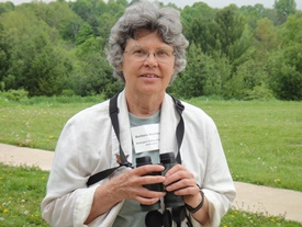 Photo of Barb Duerksen holding binoculars
