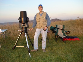 Photo of John Heasley next to telescope