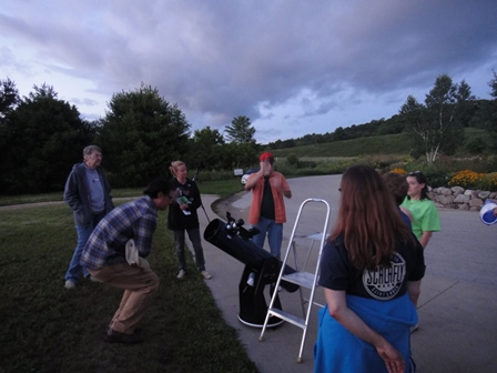 Stargazers agthered around a telescope at dusk