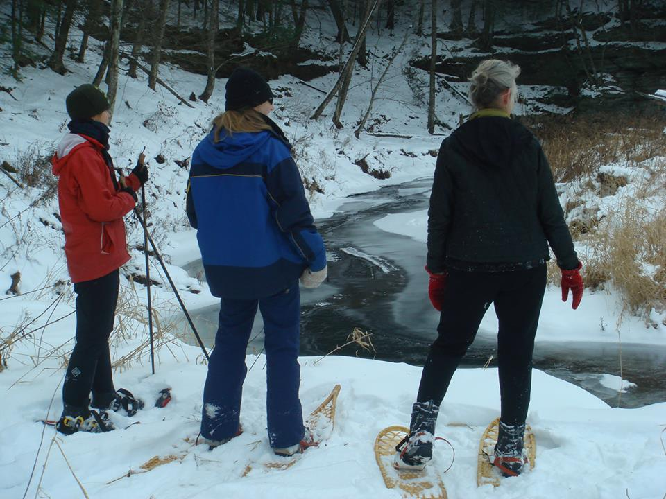 Snowshoers overlooking a stream in Winter